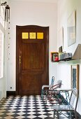 Various metal chairs against wall on chequered floor in foyer and old wooden door with square glass panels