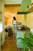 Mattgrüner Vintage Gasherd mit Kupfergeschirr in Landhausküche; Hund und Frau beim Gemüseputzen an langem Spülbecken