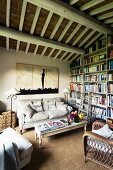 Comfortable living room with country-style seating area and bookcase below rustic wood-beamed ceiling