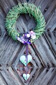 Willow wreath with purple flowers and decorative hearts on rustic front door