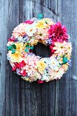 Decorative wreath of multicoloured flowers on wooden wall