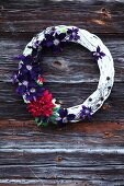Decorative wreath with clematis flowers and dahlias on wooden wall