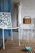 Weisser Metallstuhl mit ausgestanzten Blumenmotiven in Rückenlehne neben Acrylglastisch in Form einer transparenten Tischdecke mit Retro Radio