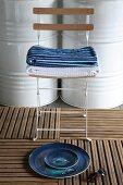 Stillleben mit Schalenset auf Holzfliesen am Boden vor Klappstuhl mit Handtuchstapel und weiss lackierte Metallfässer