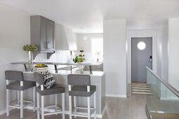 Breakfast bar with upholstered stools in front of grey and white fitted kitchen next to front door and glass balustrade