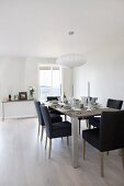 Dark blue upholstered chairs around festively set dining table in white, Scandinavian interior
