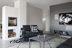 Charcoal armchair with graphic patterns on accessories between modern, free-standing fireplace and flatscreen TV