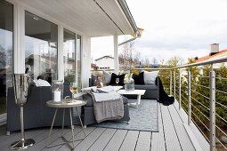 Grey sofa set, side tables and champagne cooler on wide balcony with stainless steel balustrade
