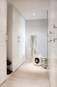 Spacious, white cloakroom with full-length mirror and black and white fabric bags