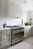 Extractor hood above electric cooker in Scandinavian cooker with pale grey fronts
