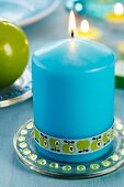 Blue candle decorated with apple-patterned ribbon