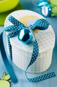 Gift box with apple bauble and polka-dot ribbon