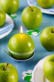 Green spherical candles and green apples on blue wooden table