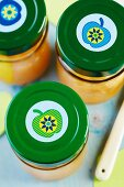 Preserving jars of apple sauce with apple stickers on lids