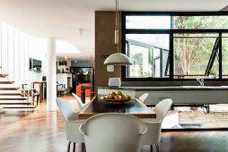 Dining area with shell chairs in light-flooded interior with floating staircase in mezzanine supports in background