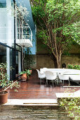 Wooden terrace with seating area in courtyard of light-flooded house in Sao Paulo