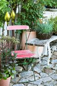 Decorative rods, old garden furniture and potted plants on stone cobbles in garden