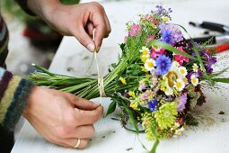 Florist's hands tying summer bouquet