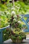 Decorative flower arrangement with garlic flowers and unripe elderberries on garden bench