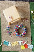 Colorful DIY wreath made of felt balls and garland with fabric letters clipped to a ribbon