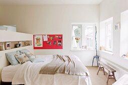 Kopfteil eines Doppelbetts als Raumteiler zur Ankleide; Magnetbord mit Kinderzeichnungen und Stuhl-Skulptur im Hintergrund