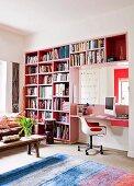 Pinkfarbenes Bücherregal mit integriertem Schreibplatz in einem Wohnzimmer