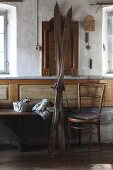 Vintage skis next to Thonet chair against wall in sparsely-furnished farmhouse parlous; Christmas gift and knitted hat on bench