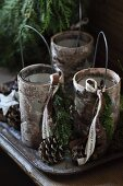 Candle lanterns with wire handles covered in birch bark with star-shaped cut-outs and festive decorations on tray
