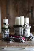 Colourful spools of wool, Christmas decorations and white pillar candles on birch logs as candlesticks on wooden surface