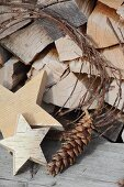 Wooden stars and pine cones in front of stacked firewood - festive, vintage atmosphere