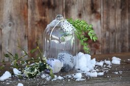 Knitted baubles under glass cover and crocheted star on weathered wooden bench decorated with snow and sprigs of mistletoe