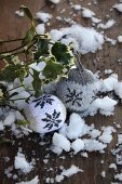 Knitted baubles with Norwegian pattern on wooden surface with snow and sprigs of mistletoe