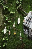 Crocheted acorns and leaves hanging from twigs on mossy boulder