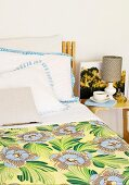 Bed with floral bedspread and scatter cushions next to coffee cup and table lamp on bedside table