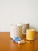 Tealight holders covered in patterned fabrics and box of matches on wooden surface