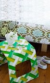 Curved plastic stool covered with green and white patterned fabric next to bed with floral-upholstered frame