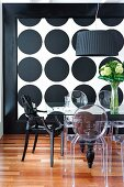 Transparent and black, plastic designer chairs around glass table in front of wall with pattern of large black circles on white background