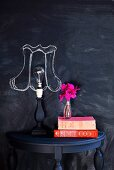 Wall painted with blackboard paint with chalk lampshade drawn around naked lamp bulb on console table