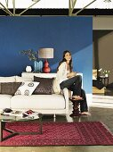 Interior with white sofa, Oriental rug and sideboard in front of blue wall; woman sitting on arm of sofa