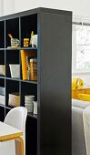 Black shelving with storage for crockery and books as partition between dining and lounge areas