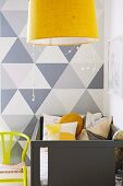 Pale grey cot against wall with painted grey geometric pattern and yellow pendant lamp in foreground