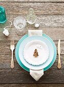 Pale blue place setting with silver cutlery and Christmas-tree biscuit on rustic, weathered wooden table