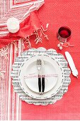 White plate arranged on sheet music place mat and red and white striped tablecloth