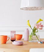 Arrangement of crockery in delicate pastel shades below white pendant lamps on dining table