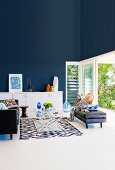Elegant living room with dark blue wall, woman reading in front of an open terrace door