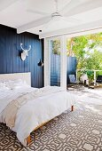 Bedroom with graphic carpet pattern, black wall covering and white stylized trophy in front of the terrace