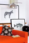 Black-framed animal graphics behind an orange sofa