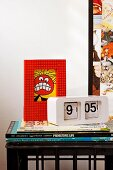Books, picture with Lego frame & retro clock on bedside table made from drinks crate