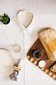 Tablecloth hand-made from men's shirt on table with wooden board, bread, spread, plate and napkin
