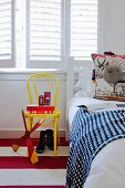 Detail of child's bedroom - toys on yellow-painted Thonet chair below window with closed white interior shutters and bed with patterned bedspread